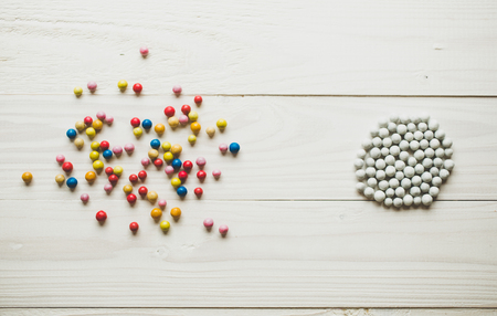Photo pour Chaotic colorful balls and organized white balls. Concept of order and chaos - image libre de droit