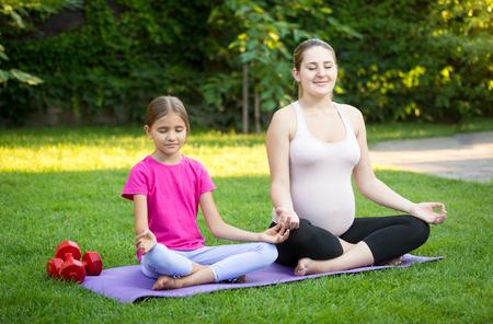 Photo pour Smiling pregnant mother practicing yoga on grass at park - image libre de droit