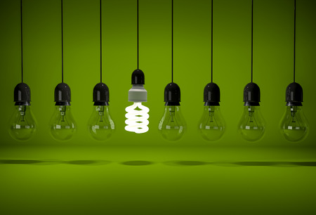 Photo pour One glowing energy saving bulb in row of dark incandescent bulbs hanging on wires over green background - image libre de droit