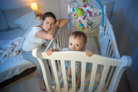 Photo for Young tired mother got asleep next to baby's crib - Royalty Free Image