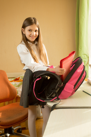Beautiful girl in school uniform posing with bag