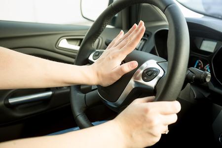 Photo pour Closeup image of annoyed woman driving car and honking - image libre de droit