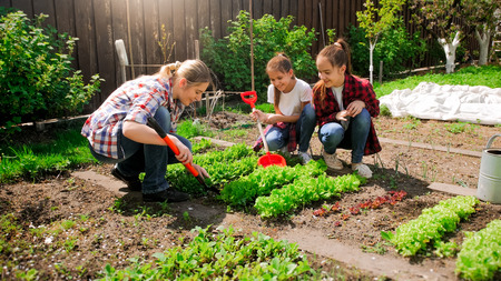 Photo pour Happy young woman with daughters planting seeds in garden - image libre de droit