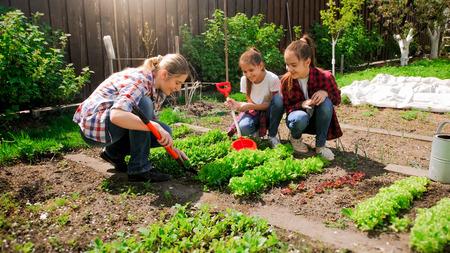 Foto de Happy young woman with daughters planting seeds in garden - Imagen libre de derechos