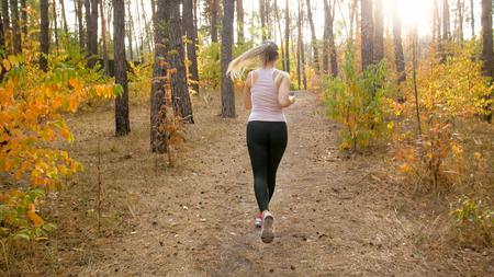 Sexy slim woman in sport legging running in park at bright sunny morning