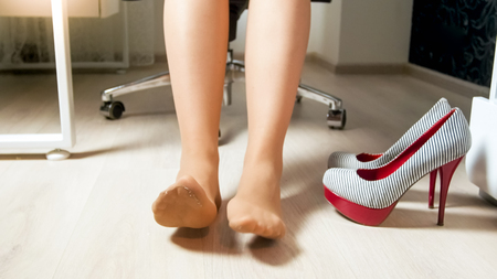 Closeup photo of young businesswoman stretching tired feet after workday in office