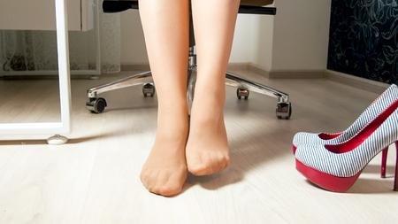 Photo pour Closeup image of businesswoman resting feet under desk - image libre de droit