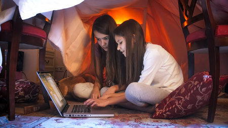Foto de Two cute girls in pajamas sitting with laptop at tent made of blankets - Imagen libre de derechos