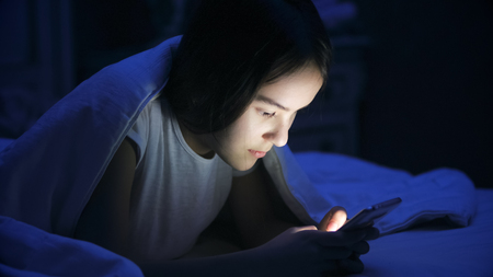 Portrait of teenage girl lying in bed at night and using smart phone
