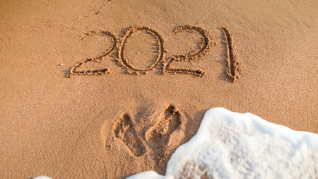 Photo for Closeup photo of 2021 numbers written on sand and footprints on sea beach. Concept of New Year, Christmas and travel on winter holidays. - Royalty Free Image