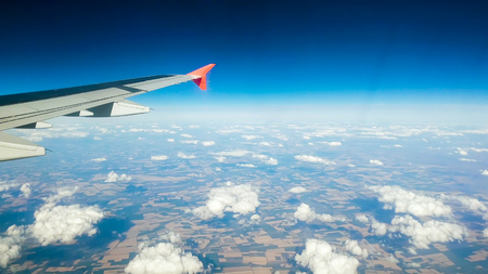 Photo pour View from passenger seat on airplane wing and clouds against blue sky - image libre de droit