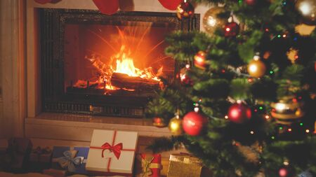 Photo pour Toned Christmas background with Christmas gifts and presents under Xmas tree and burning fireplace - image libre de droit