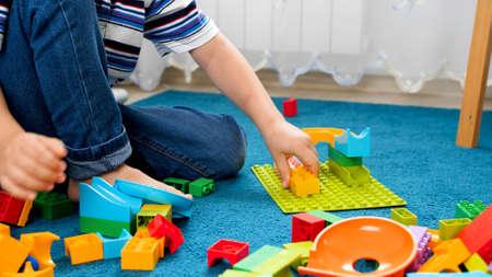 Photo pour Closeup image of little boy assembling colorful toy constructor on carpet - image libre de droit