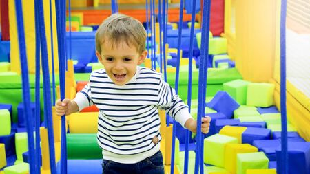Photo pour Portrait of happy smiling boy playing and climbing on ropes on the playground at amusement park - image libre de droit