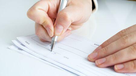 Photo pour Closeup image of person signing banking cheque - image libre de droit