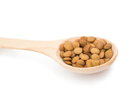 pulses in a wooden spoon isolated on a white background