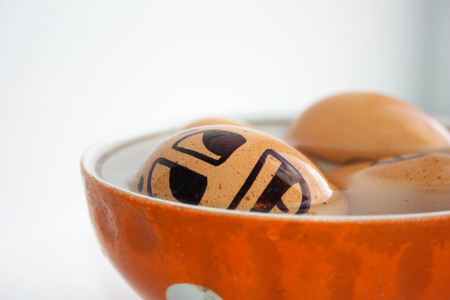 Eggs with painted face. Photo for your design. Egg to swim in a plate. Joy and rest. Vacation