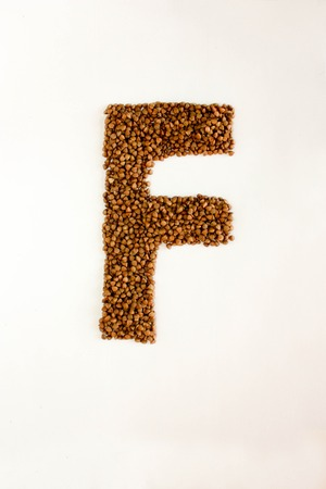 F the letter. alphabet of buckwheat porridge. buckwheat grain. concept of healthy eating. photo for your design. vertical orientation of the sheet
