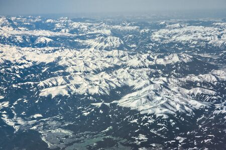 Photo pour Blue Alps mountains with snowy white peaks from an airplane - image libre de droit