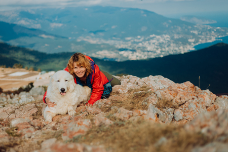 Foto de Happy cheerful white dog, shepherd dog of the Abruzzi Maremma with a woman in red lay on field n the mountains. sea and city view - Imagen libre de derechos