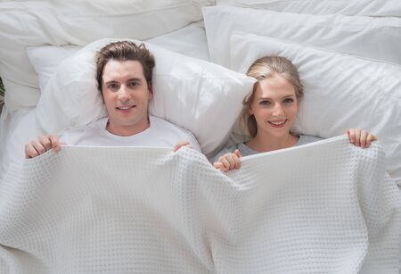 Photo for Couple young in love smiling lying cover under white blanket in bed - Royalty Free Image