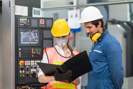 Photo pour Female engineer wearing face mask with safety vest and protective helmet with male engineer looking document operating control CNC Machinery at factory - image libre de droit