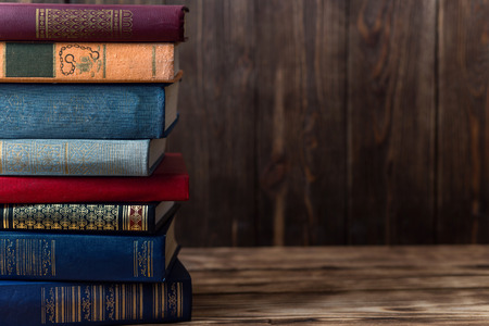 Photo for Many old books on a wooden background. The source of information. Open book indoor. Home library. Knowledge is power - Royalty Free Image