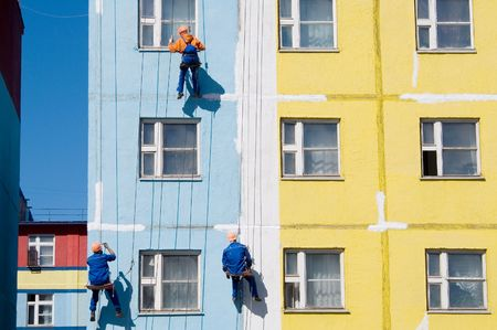 House painters paint the facade of building
