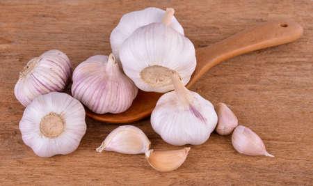 Foto für garlic in a wooden spoon on a wooden floor - Lizenzfreies Bild
