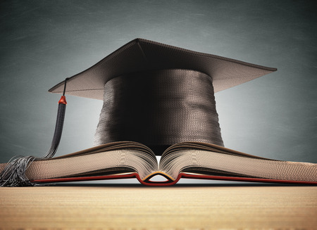 Graduation cap over the book with blackboard on background. Clipping path included.