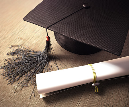 Graduation cap with diploma over the table. Clipping path included.