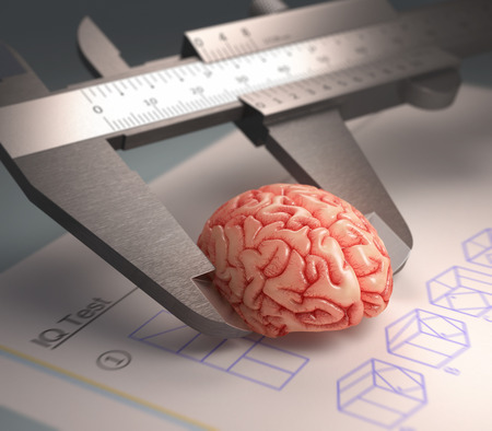 Caliper ruler measuring a human brain. Over the table a IQ Test in a concept of the human intelligence.