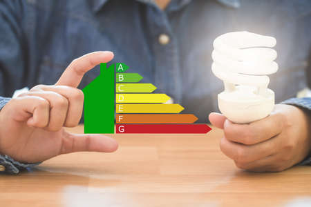 Hands holding spiral bulb and symbol energy efficiency, Saving energy efficiency and and and green energy concept.