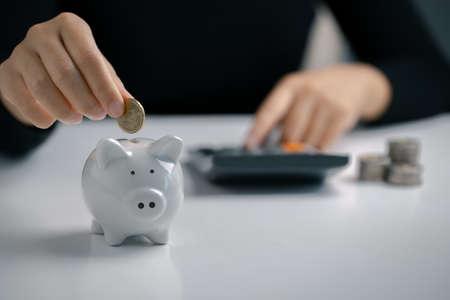 Foto de Hand putting coin to piggy bank and using calculator, Saving money and calculating financial. - Imagen libre de derechos