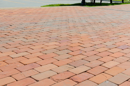 Photo for Pavement of red, dark red and orange bricks beside carriageway at summer day - Royalty Free Image