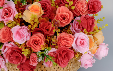 Photo for A fragment of a bouquet of artificial rose flowers red, pink yellow in a basket on a gray background. - Royalty Free Image