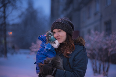 Girl walking with a cat in winter