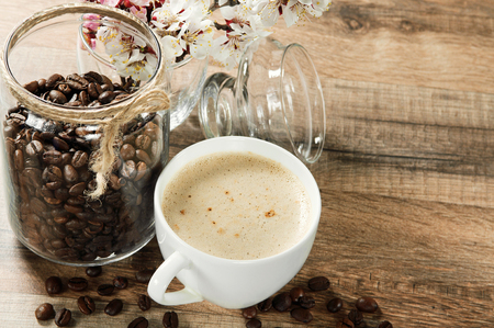 Fragrant coffee on a wooden table. next to a cup of coffee, a jar of coffee beans and a bouquet of blossoming apricot