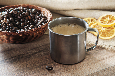 Coffee in a metal cup, standing on a wooden table. Next to a cup of coffee costs wicker plate with coffee beans and dried orange slices