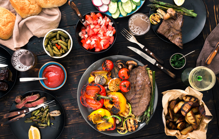 Grilled steak with grilled vegetables, beer and wine on a dark wooden table, top view. Dinner table concept