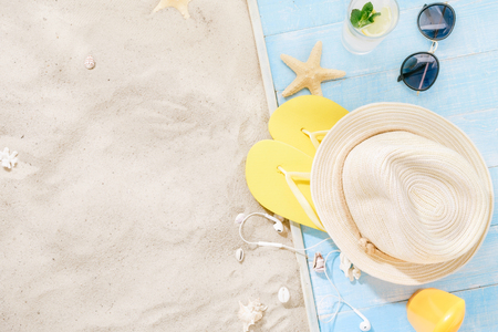 Travel vacation concept. Traveler accessories on sand. Straw hat, sunglasses, flip flops, cocktail, sunblock with copy space. Summer background