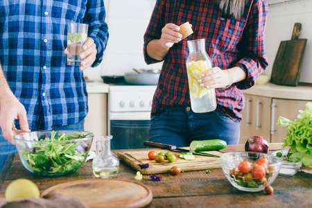 Couple is cooking healthy simple food at home in the kitchen. Healthy food concept. Couple preparing summer salad