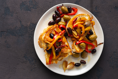 Sandwiches with grilled peppers, olives and garlic on a dark