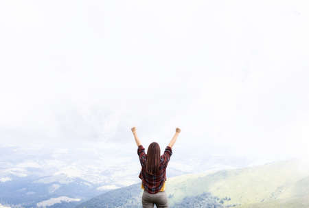 Photo pour Freedom concept. Woman with hands up standing on top of mountain enjoying the view - image libre de droit