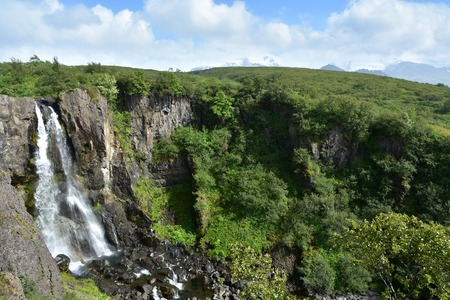 waterfall at Skaftafell in Vatnajokull National Park in Iceland with beautiful green landscape surrounding reach the waterfall.
