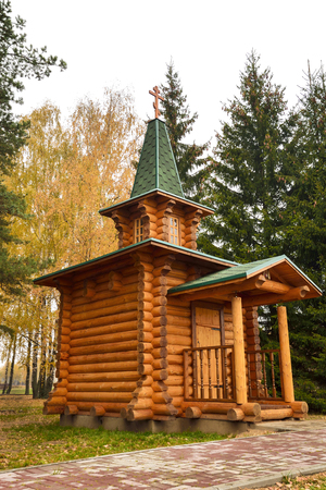 a small wooden chapel with a green roof