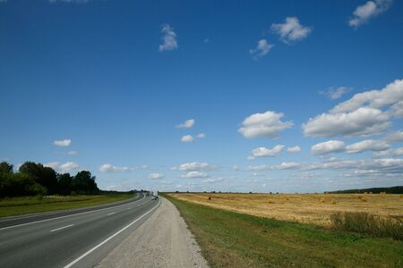Photo pour Intercity route passing fields and forests on a summer day with cloudy sky - image libre de droit