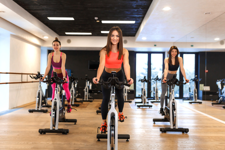 Photo for Group of young slim women workout on exercise bike in gym. Sport and wellness lifestyle concept. - Royalty Free Image