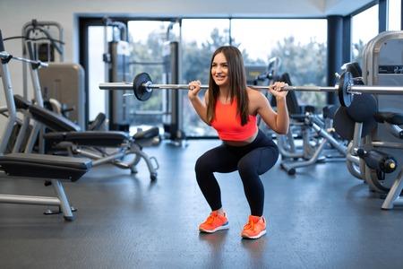 Foto de slim handsome young woman in sportswear squats with a barbell on the shoulder in the gym. - Imagen libre de derechos