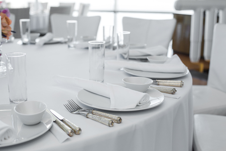 Photo for served table in the restaurant. clean white dishes layout on a white tablecloth. - Royalty Free Image